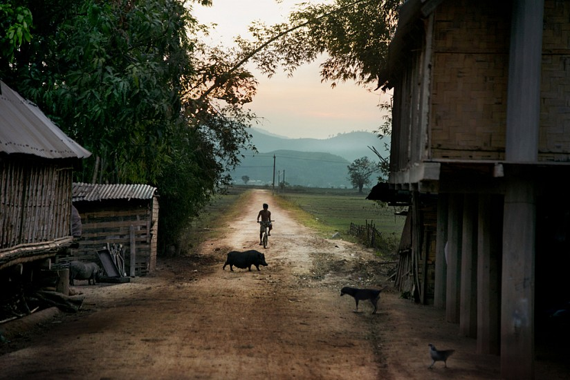 Steve McCurry, Boy Rides Bike Down Dirt Road 2013, FujiFlex Crystal Archive Print
