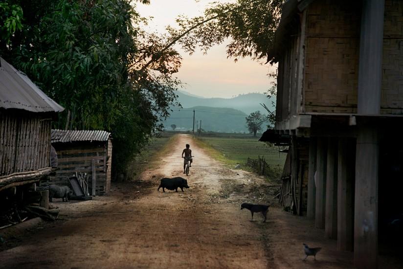 Steve McCurry, Boy Rides Bike Down Dirt Road 2013, FujiFlex Crystal Archive Print