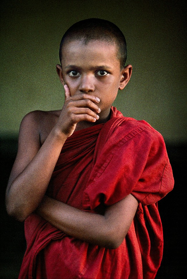 Steve McCurry ,   Novice Monk Covers Mouth  ,  1995     FujiFlex Crystal Archive Print     Price/Size on request